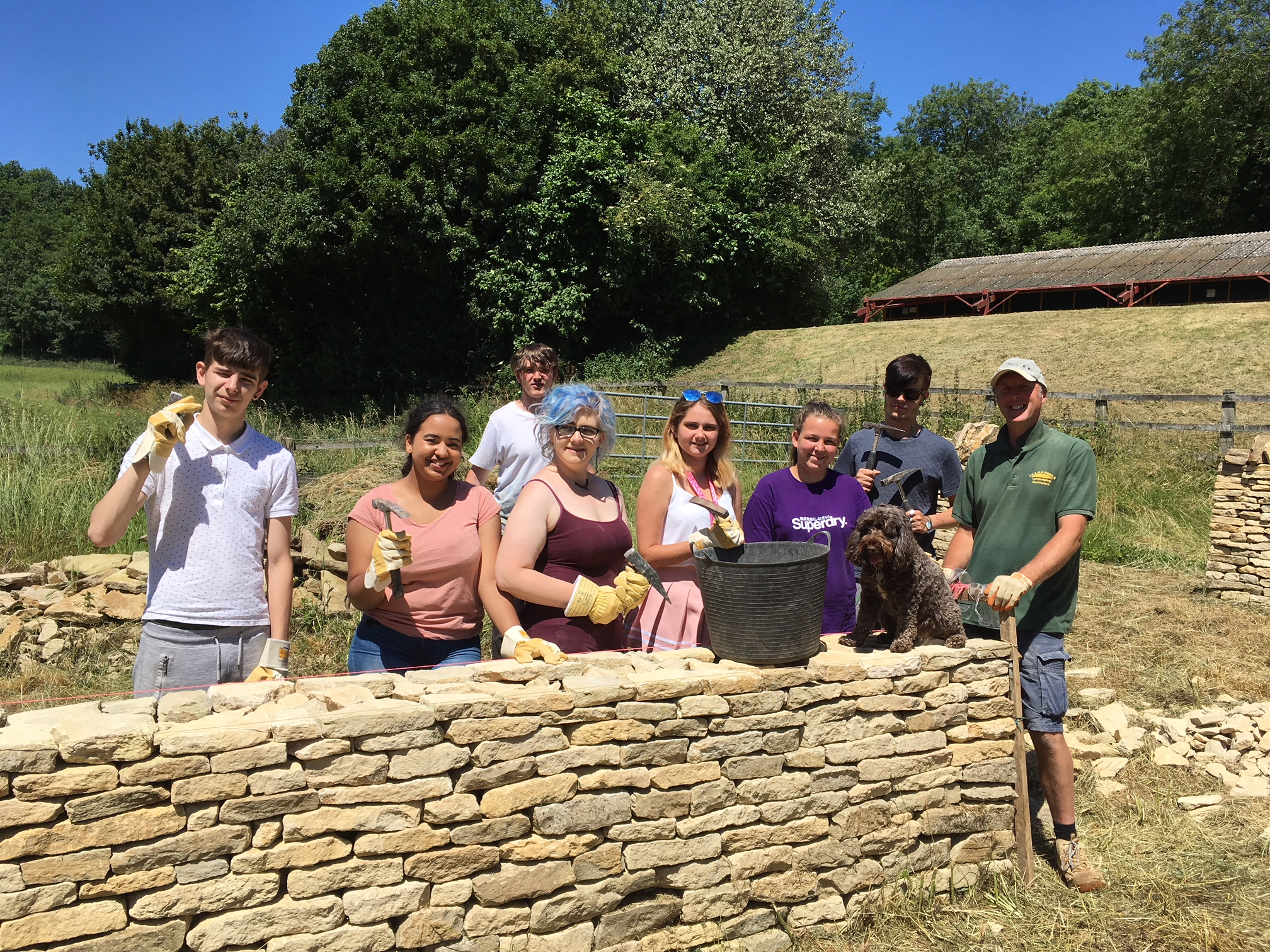 A group of people by a dry stone wall in the Cotswolds