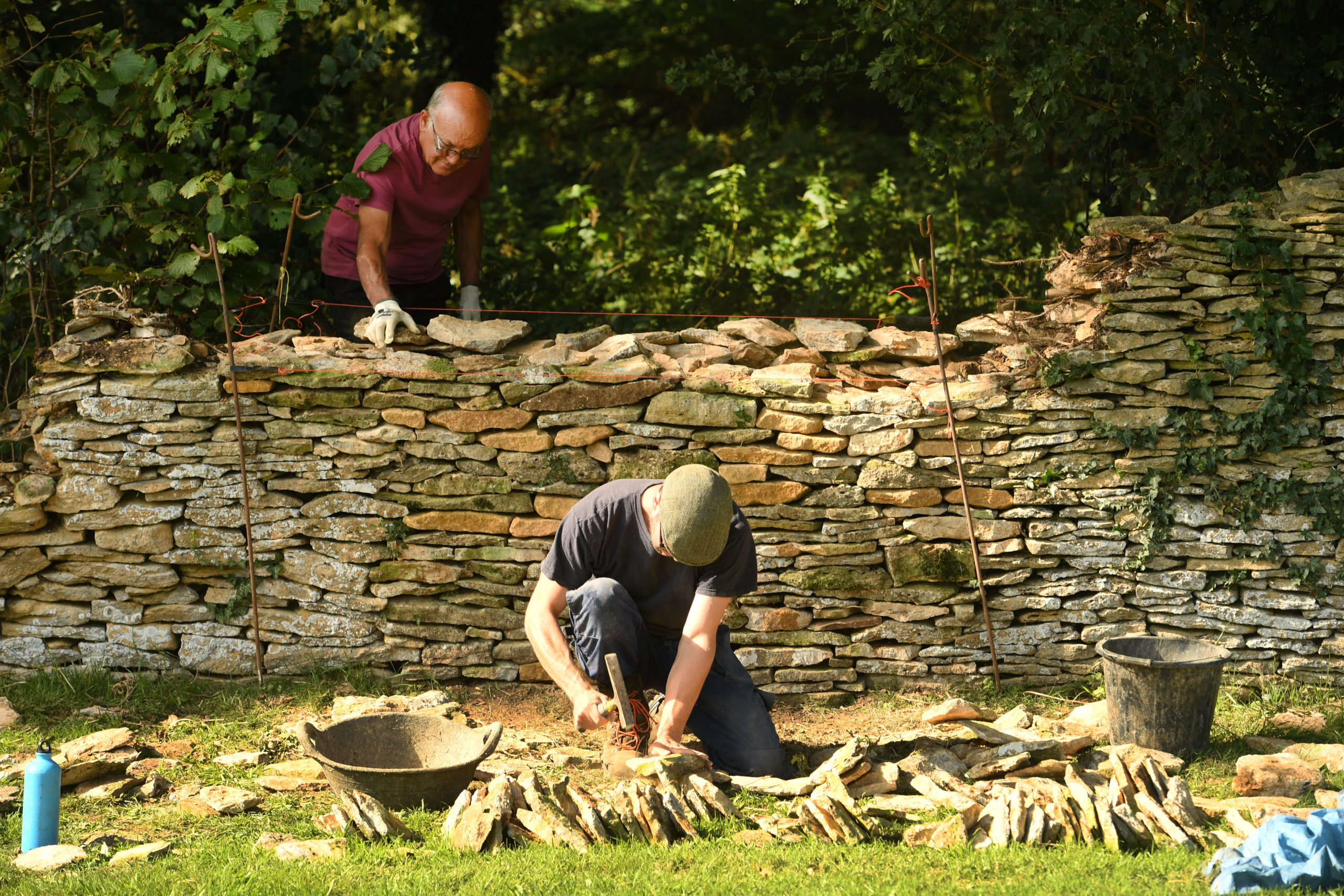 Two men building a dry stone wall