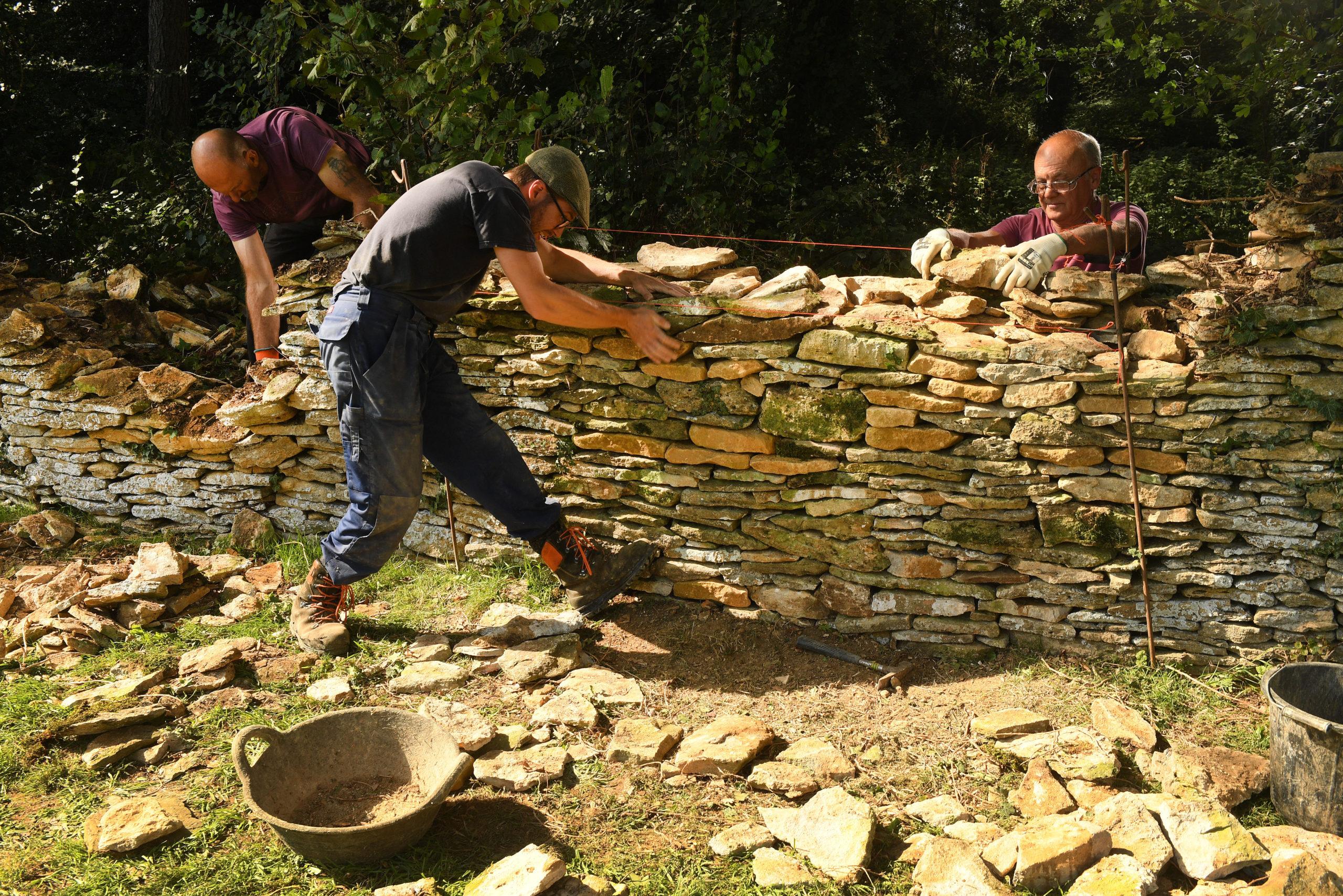 Three men building a dry stone wall