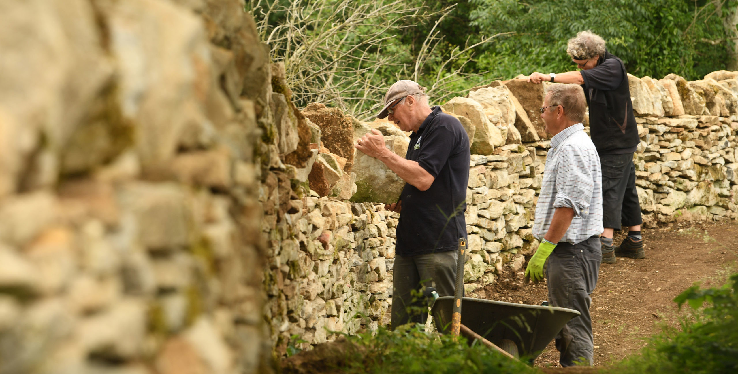 A group of people helping to repair a dry stone wall together.