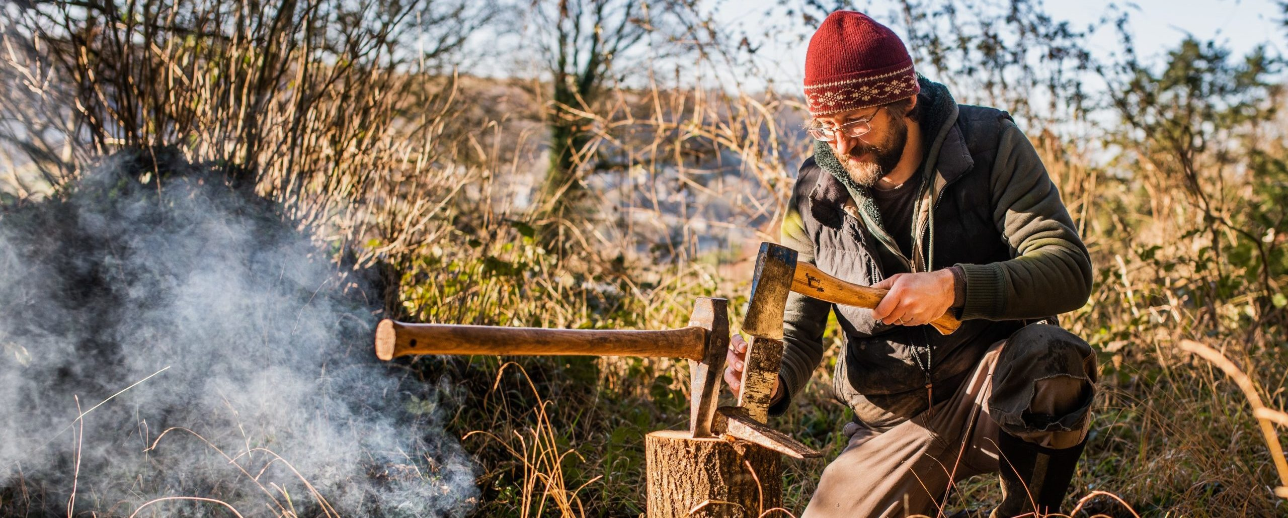 Image of man splitting wood with an axe beside a small camp fire
