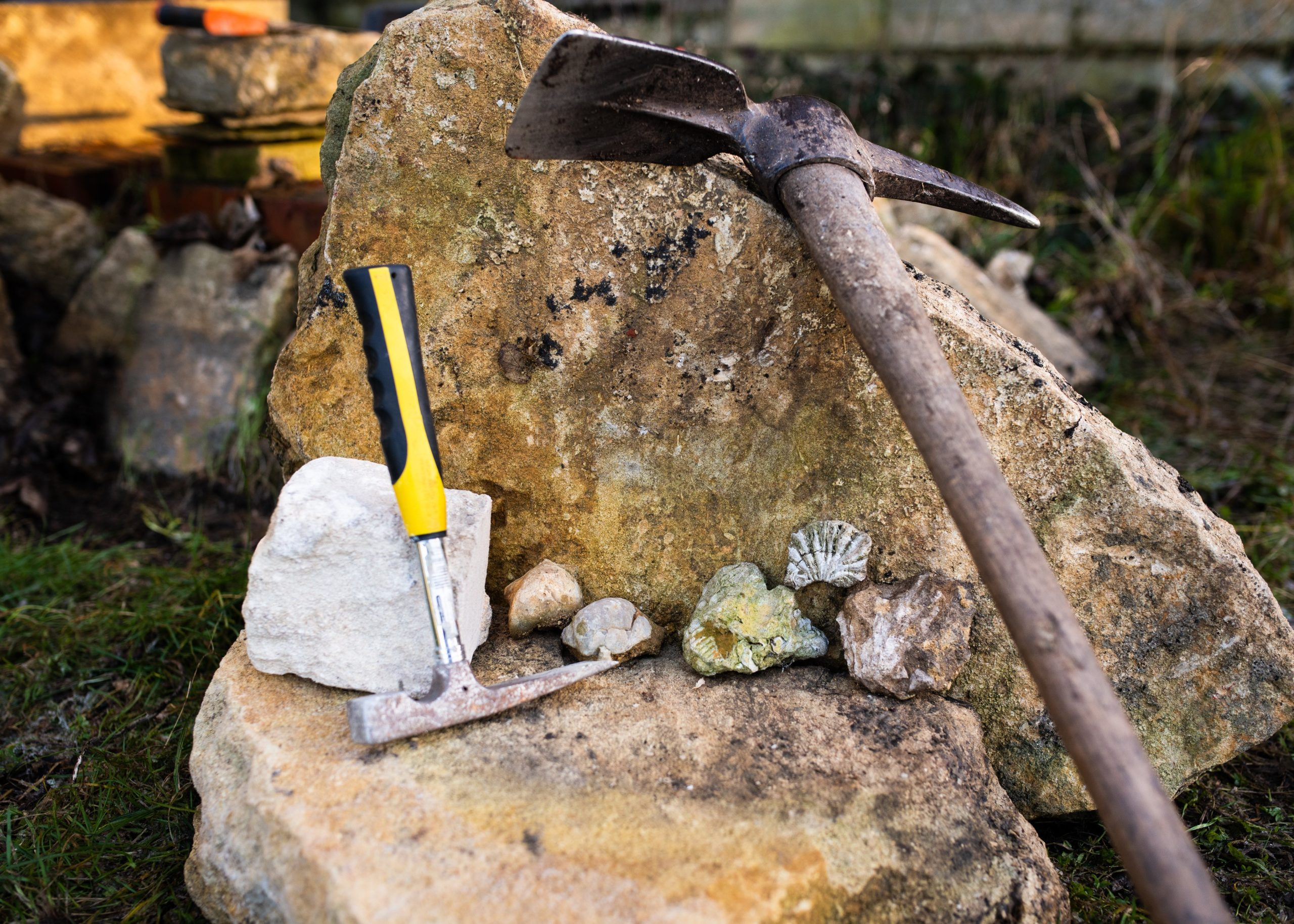 Image of stone carving tools resting against large rock in the autumn sun