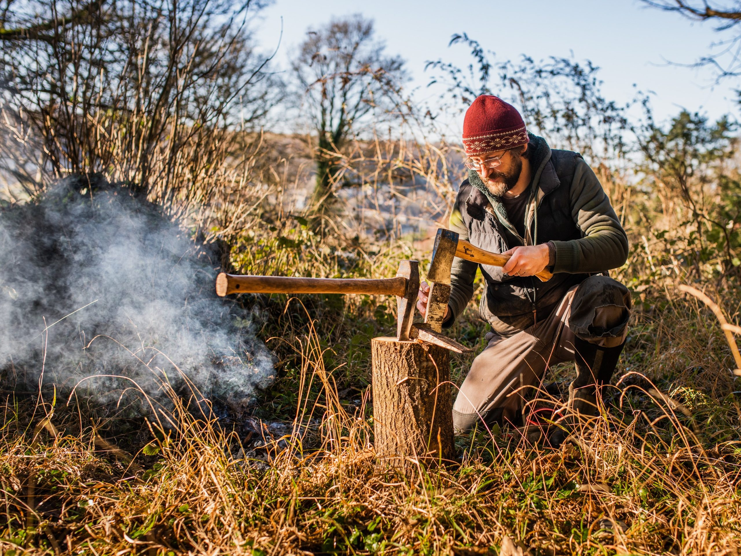 A man in a red woolly hat kneels near an outdoor campfire to chop firewood with a kindling splitter whilst a larger axe sits embedded in the upturned log in front of him.
